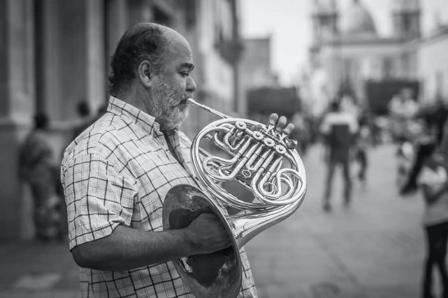 A man playing the hardest instrument to play, the French horn.