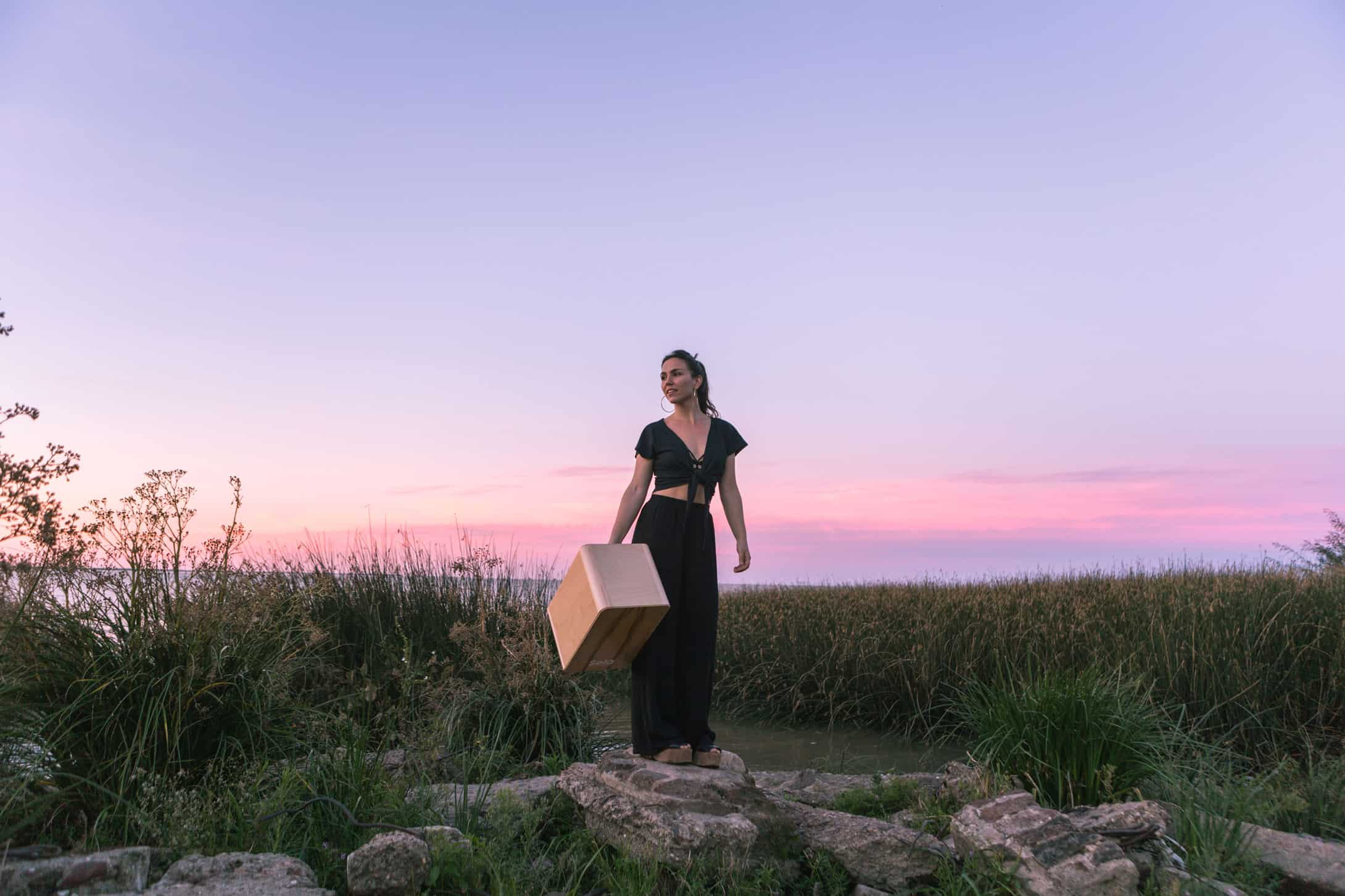 A girl holding her Cajon drum box during sunset.
