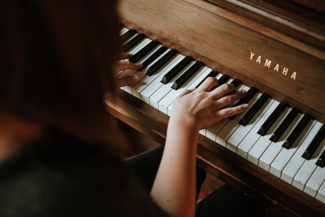Girl playing a Yamaha piano.