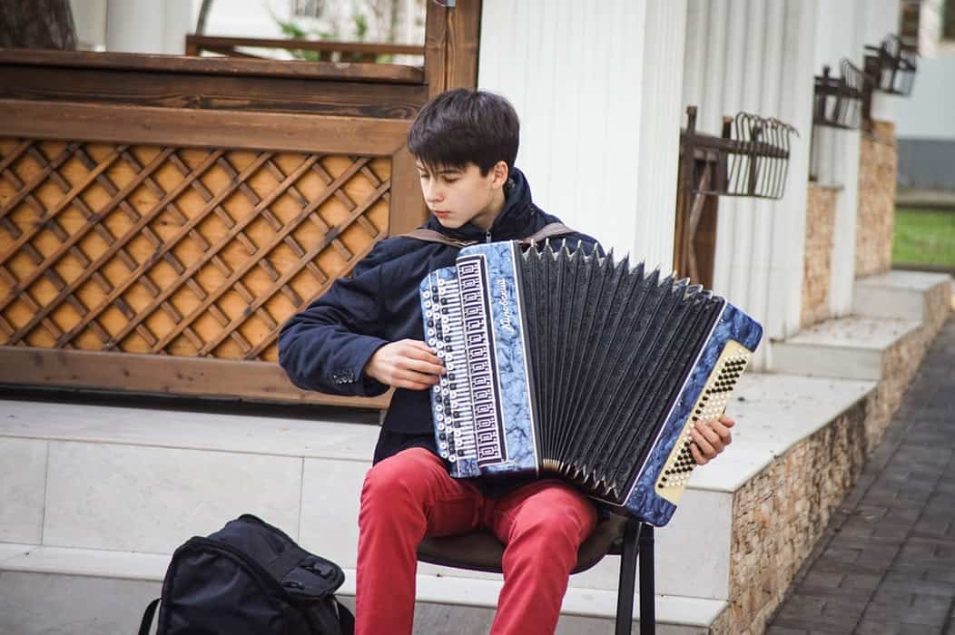 Young boy playing the accordion.