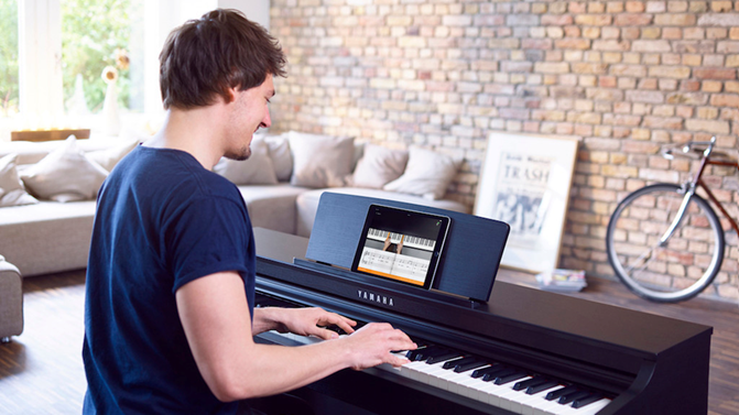 A person learning to play piano with Flowkey.